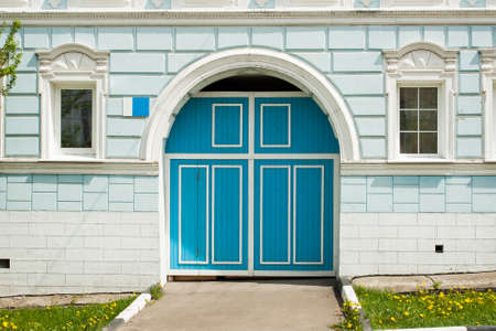 Blue Classic Wooden Door Entrance With Arch In Stone Wall Of Residential Building With Windows. Background Texture. Фото со стока