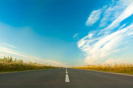 Wide Asphalt Gray Road On Bright Blue Sky Background With Clouds In Spring. Reklamní fotografie