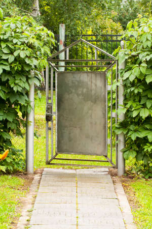 Ajar Gate. Old Painted Metal Gray Gate In After Rain Garden Summer Day. Фото со стока