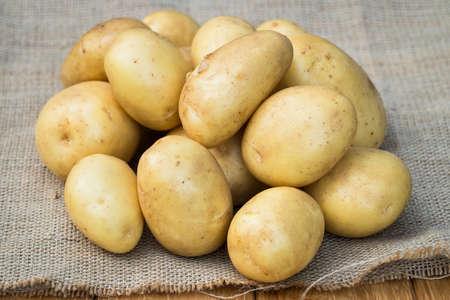 Frische Bio-Kartoffeln. Junge gelbe Kartoffeln auf Sackleinen mit Textur hautnah. Standard-Bild