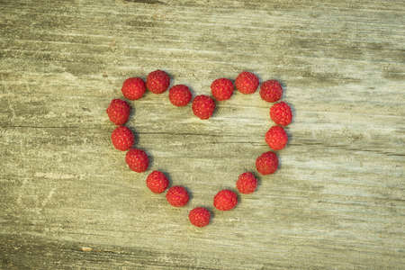 Shape Of Heart Of Fresh Sweet Berries Raspberry On Gray Wooden Board Background Top View. Stok Fotoğraf