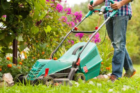 Young Male Gardener Mow Grass With Lawn Mower In Garden In Summer. Working In Garden.