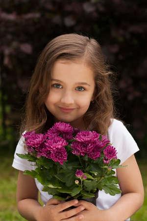 Portrait Of Cute Little CaucasianWhite Girl With Fresh Bouquet Flowers Chrysanthemum In Summer Garden Outdoors.