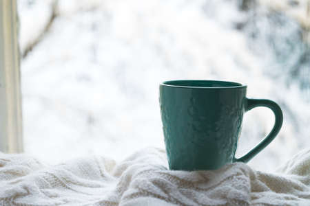 Cup Of Hot Coffee With White Warm Plaid On Windowsill Window Of House Winter. Stock Photo