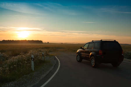 Beautiful Landscape With  Black Car On Asphalt Road Under Blue Sky With Sunset Of Sun In Early Dawn Summer. Reklamní fotografie