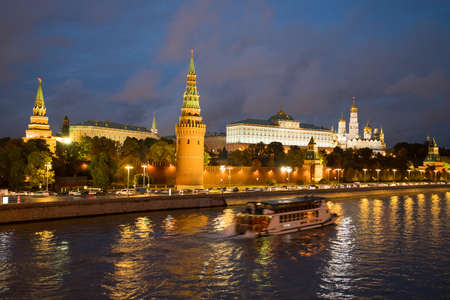 Moscow, Russia. Beautiful View On Moscow Kremlin With Illuminations From Lamps And With Floating Motor Ship On Coast Of Moscow River Under Blue Dramatic Sky In Evening Day In Autumn. 版權商用圖片