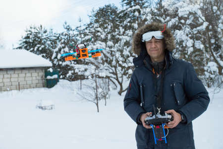 Drone Quad Copter Hovers In Front Of Man Pilot With Remote Controller In His Hands Outdoors Winter.