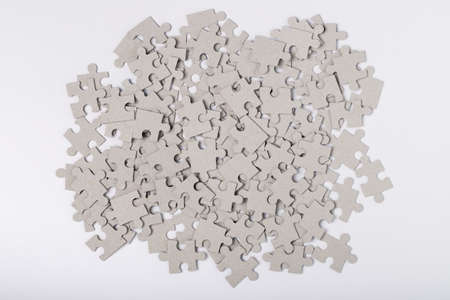 Heap Of Jigsaw Puzzles Grey Color On White Paper Background Top View. Assembly Of Puzzles. Developing Game. Stockfoto