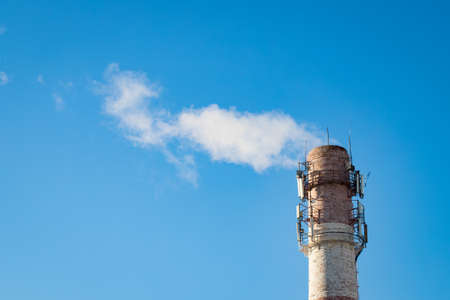 Close Up Of Old Factory Pipe (Chimney) With Smoke On Blue Sky Background. 写真素材