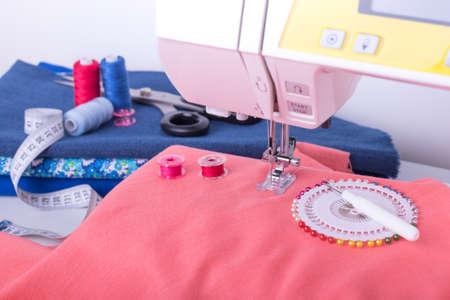 Verschiedenes Zubehör zum Nähen, Nähmaschine und Stoffe hautnah. Arbeit in der Handarbeitswerkstatt. Standard-Bild