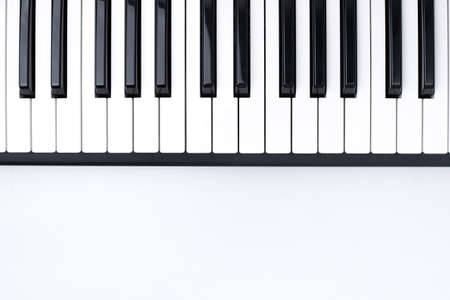 Black And White Piano Keys On White Background Of Wooden Table In Musical Studio Top View. Foto de archivo