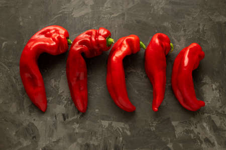 Five fresh ugly red sweet peppers lie on a dark background. Place for text. Ugly food