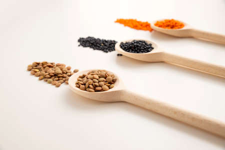 a wooden spoon with brown lentils close-up, in the background are two spoons with black and orange lentils out of focus. White background