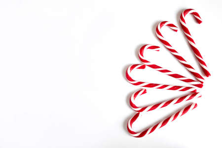Six Christmas lollipops, New Years red and white candies in the shape of a cane are fan-shaped on a white background. Holiday concept, greeting card. Copy space. Zdjęcie Seryjne