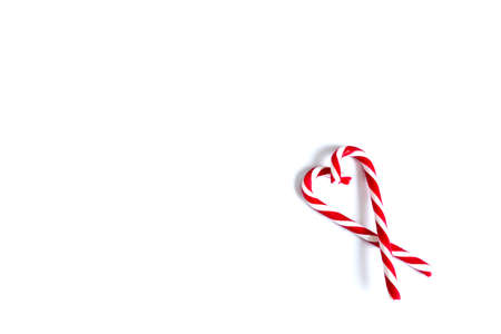 Two Christmas red and white candies, Christmas candy canes folded in the shape of a heart on a white background. place for text. Zdjęcie Seryjne