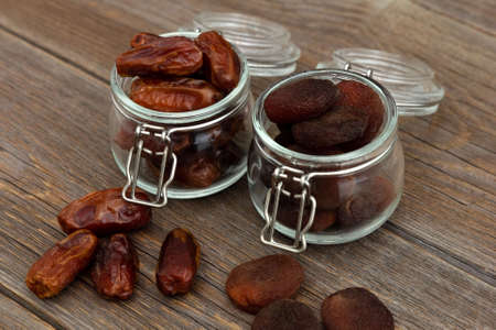 Organic bio dried dates and dried apricots, apricot in glass jars stand on an old rustic wooden table. Dried fruits. Healthy snack