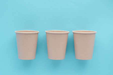 Three eco-friendly bamboo reusable cups on a blue background. Environmental protection, no waste
