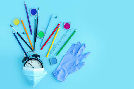 Stationery, crayons, brushes, medical mask and a glove around a black alarm clock. Back to school, starting school after quarantine and vacation in a new reality. Copy space