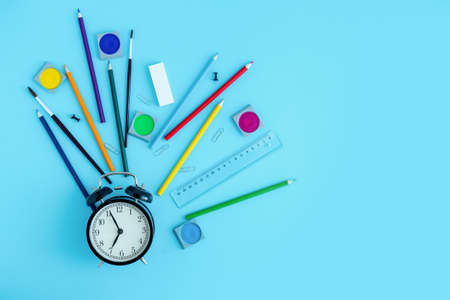 Stationery, crayons, brushes and paints around a black alarm clock. Back to school, start of the school year. Copy space Imagens