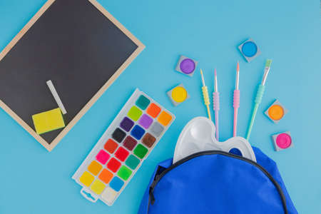 School, stationery poured from a blue backpack or knapsack on a light background, next to a school graphite board. Learning after vacation and quarantine. Place for text