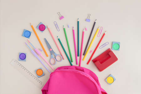 School, office supplies poured from a pink backpack or knapsack on a light background, top view. Back to school, learning after vacation. Place for text