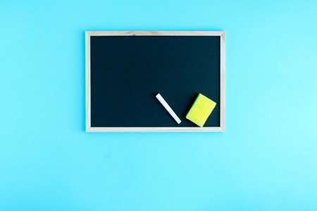 Graphite school board with a piece of chalk and a sponge on a blue background. Place for your text. Beginning of a new school year Banque d'images