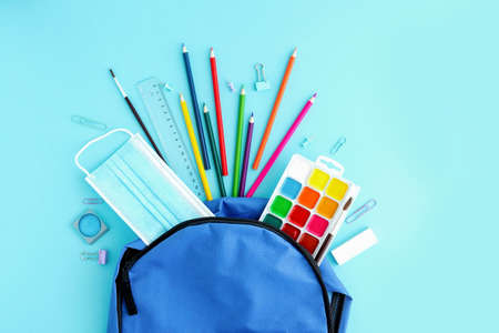 School supplies and a protective medical mask poured out of a blue backpack or knapsack on a light background, top view. Back to school, study after vacation and quarantine. Place for text Banque d'images