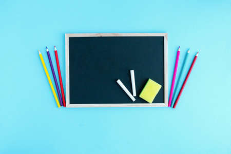 Graphite school board with a piece of chalk, a sponge and a medical protective mask on a blue background. Copy space. The beginning of the new school year. Virus protection in educational institution Banque d'images