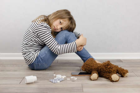 Psychological health of children and adolescents. A depressed girl sits on the floor, pills lie next to her. Misunderstanding of parents, bullying of children. Place for text.