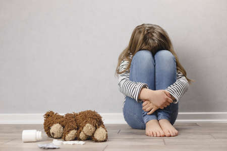 Sad teenager girl, schoolgirl in depression sits on the floor near the wall, next to a teddy bear and pills
