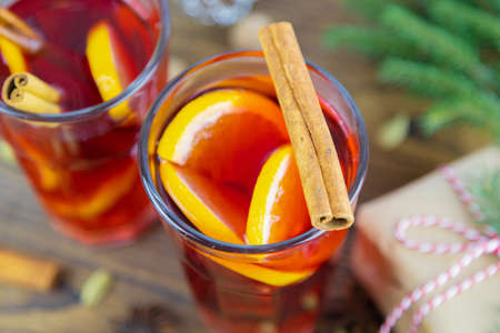 Close-up of two glasses with hot wine, mulled wine, punch, decorated with a cinnamon stick, Christmas tree, gift box in the background. Winter drink