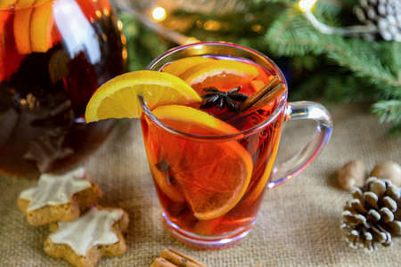 A glass of hot mulled wine with fresh orange slices and cinnamon sticks nearby on a beige background. New Year's, winter drink.