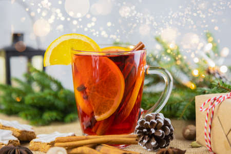 A glass of hot wine, mulled wine in a New Year's setting with bokeh in the background. Christmas, winter hot drink.