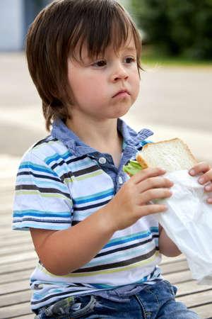 Schoolchildren, preschooler, boy eating his lunch, snack, breakfast in the school yard. Food for children in educational institutions, kindergartens. Healthy eating. Stock fotó