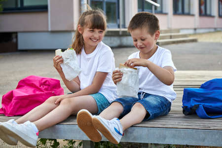 Schoolchildren boy and girl laugh and eat their lunch, snack, breakfast in the school yard. Food for children in educational institutions, kindergartens.