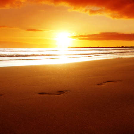 Footprints on the beach at sunset. photo
