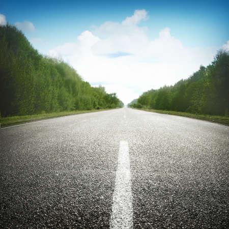 carretera: Carretera vac�a bajo el cielo azul con nubes.