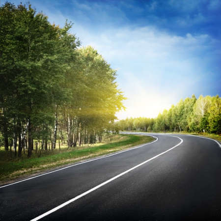 autopista: Carretera vac�a curva, cielo azul y el sol.