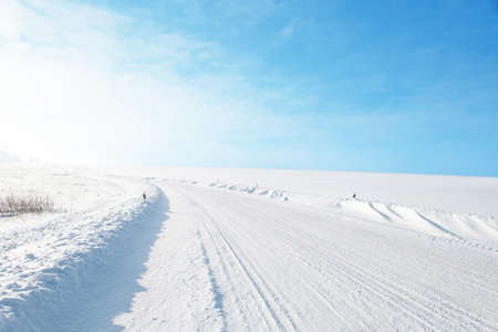 snow field: Winter road under blue sky.