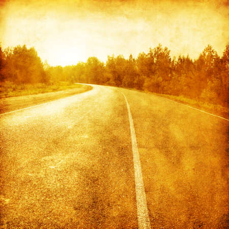 Grunge image of country asphalt road at sunset. photo
