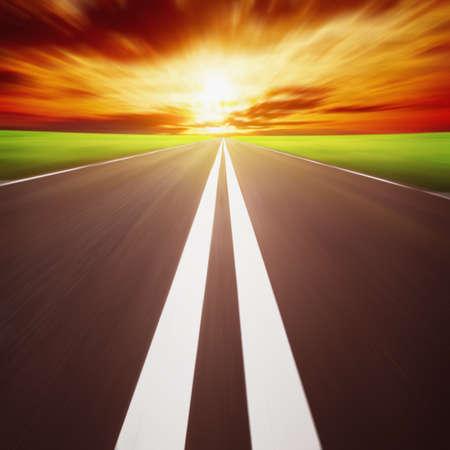 Route avec le flou de mouvement au coucher du soleil