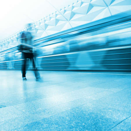 blue toned:  Motion blurred passenger walking in subway station