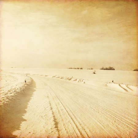 Old style photo of empty winter road. photo