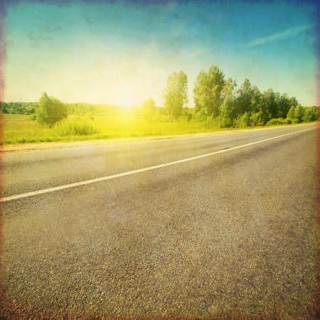 tar paper: Grunge style image of country asphalt road at sunset. Stock Photo