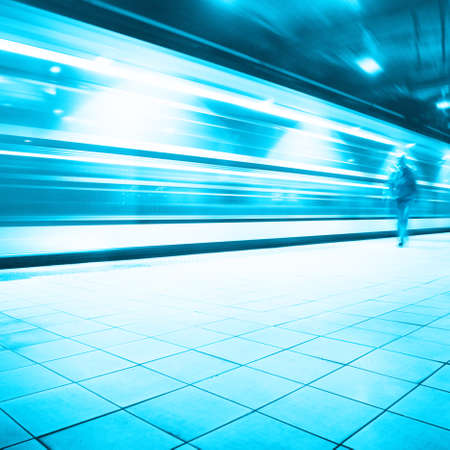 blur subway: Train in motion blur and blurred commuter walking in subway station   Stock Photo