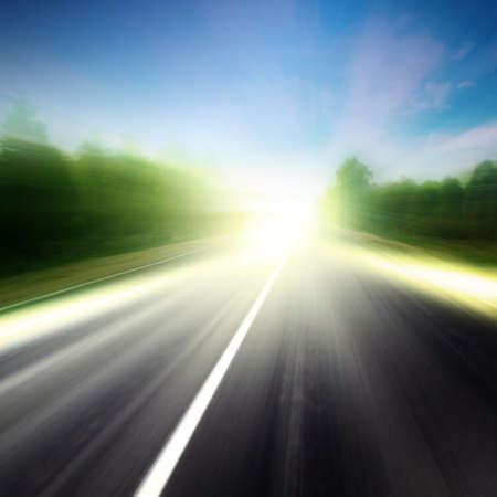 Image of asphalt road in motion blur at sunset.  Stock Photo