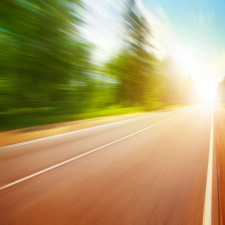 road marking: Country asphalt road in motion blur and sunlight. Stock Photo