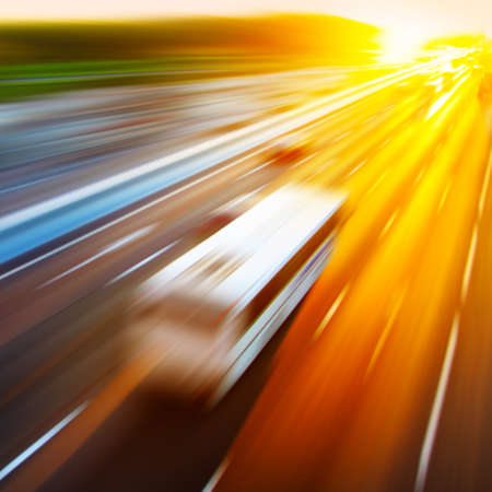 blurred: Motion blurred image of driving bus during sunset. Stock Photo
