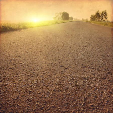Country asphalt road at sunset in grunge and retro style. Stock Photo
