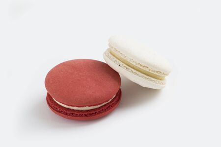 Closeup photo of two delicious french dessert macaroons, vanilla and cranberry taste.